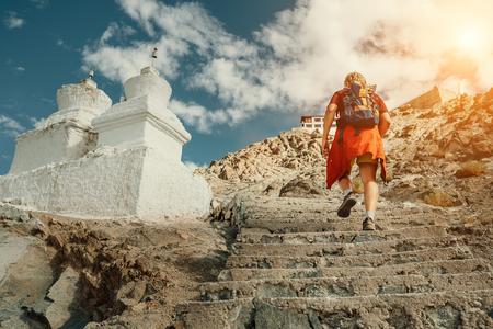 Photo pour Tourist man climbs up stairs to tibetan holy place in Himalaya mountain - image libre de droit