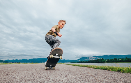 Photo for Young skateboarder make a tricks with skateboard - Royalty Free Image