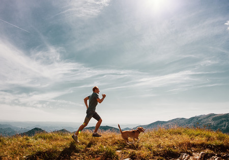 Photo pour Man running with his beagle dog on mountain top - image libre de droit