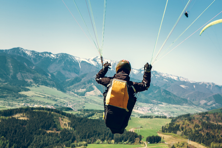Photo for Paraglider is on the paraplane strops - soaring flight moment - Royalty Free Image
