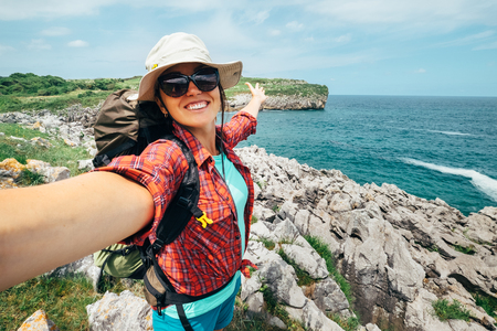 Photo pour Happy woman backpacker traveler take a selfie photo on amazing ocean coast. Asturias. Spain - image libre de droit