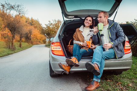 Photo pour Tea party in car trunk - loving couple drinks hot tea from thermos flask sitting in car trunk - image libre de droit