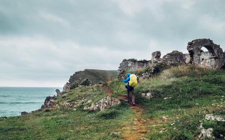 Foto de Traveler on the sea coast near the Llanes,  Asturias, northern Spain - Imagen libre de derechos
