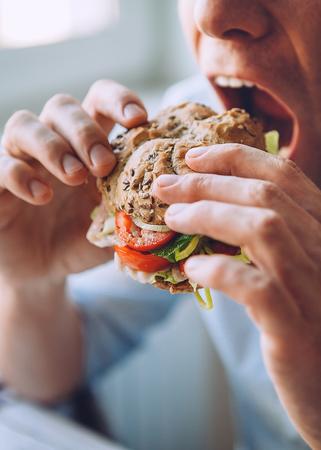 Foto de Hungry man eats a big sandwich - Imagen libre de derechos