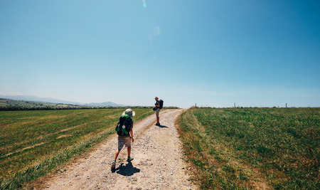 Foto de Father and son backpacker travelers walk on countryside road across field - Imagen libre de derechos