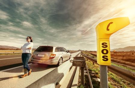Foto de SOS service point on highway - woman driver has a problem with car - Imagen libre de derechos