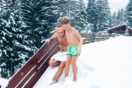 Photo pour Father and son refresh in snow after hot sauna  - image libre de droit