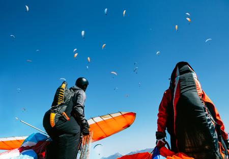 Foto de Two paragliders with full flight equipment look on soaring another paragliders in sky - Imagen libre de derechos