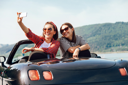 Photo pour Two female freinds take a selfie photo in cabriolrt car during their summer voyage - image libre de droit