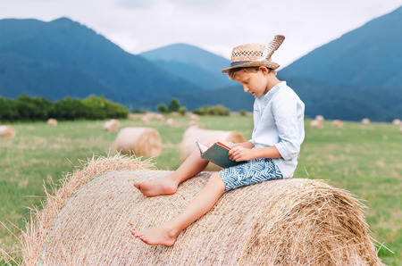 Photo pour Reading boy sits over the haystack roll on the mountain field in countryside - image libre de droit