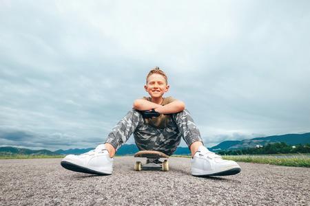 Photo pour Boy sits on skate board  - image libre de droit