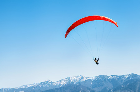 Photo pour Sportsman on red paraglider soaring over the snowy mountain peaks - image libre de droit