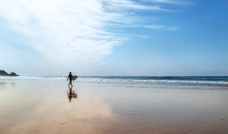 Foto de Surfer figurine with surfboard on the coast line at morning time - Imagen libre de derechos