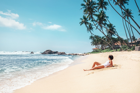Foto de Woman takes sunbath on tropical beach. Island paradise - Imagen libre de derechos