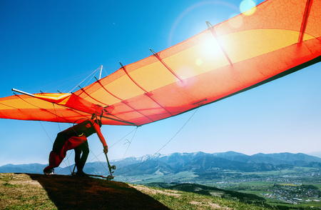 Photo for Man with hang-glider starting to fly from the hill top - Royalty Free Image