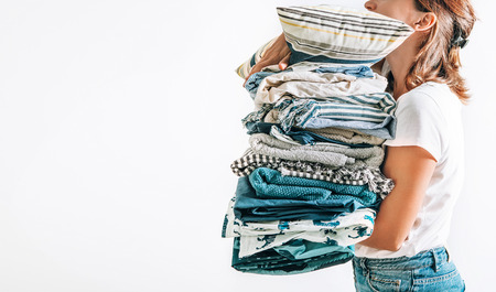 Photo for Woman takes in hands big pile blue and beige blankets, towels and other home textile - Royalty Free Image