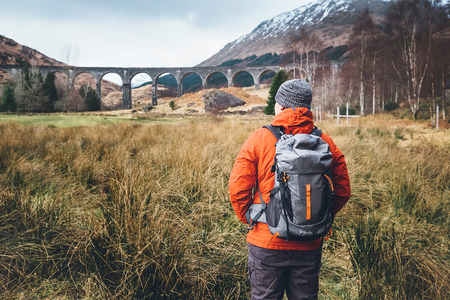 Photo for Hiking, walk with backpack, active lifestyle concept image. Man traveler walks neaar famous Glenfinnan viadukt in Scotland - Royalty Free Image