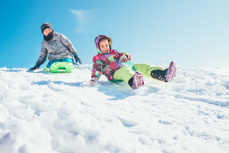 Photo pour Brother and sister slide down from the snow slope. Winter time pleasures - image libre de droit