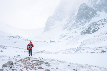 Photo pour Climber walks alone in high mountains at windy snowy weather - image libre de droit
