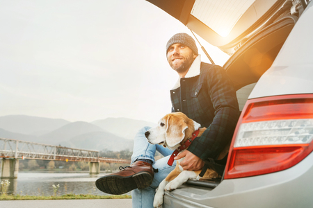 Foto de Man with beagle dog siting together in car trunk. Late autumn time - Imagen libre de derechos
