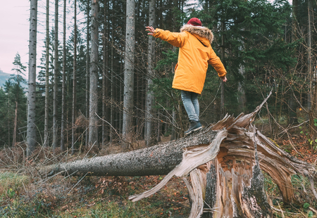 Photo for Boy in bright yellow puffer jacket walks in pine forest balancing on the falling tree. - Royalty Free Image