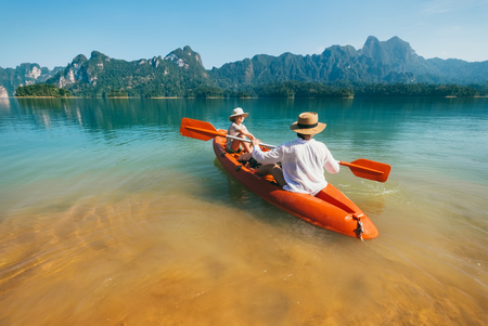 Foto de Mother and son floating on kayak together on Cheow Lan lake in Thailand - Imagen libre de derechos