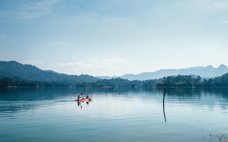 Foto de Mother and son floating on kayak together on calm water of Cheow Lan lake in Thailand - Imagen libre de derechos