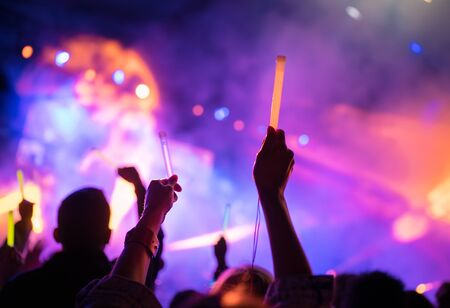 Foto de Young teenager girl fan raised up two hands with colored glowing sticks supporting favorite popular band on the night concert. - Imagen libre de derechos