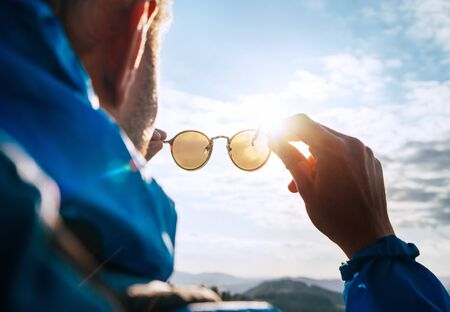 Foto de Backpacker man looking at bright sun through polarized sunglasses  enjoying mountain landscape. - Imagen libre de derechos