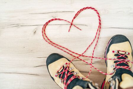Photo for Conceptual image of the pair new trekking boots on the wooden floor  with released long shoelaces behind lying in heart shape. - Royalty Free Image