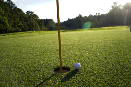Photo pour Golf ball on the edge of hole on putting green on golf course - image libre de droit