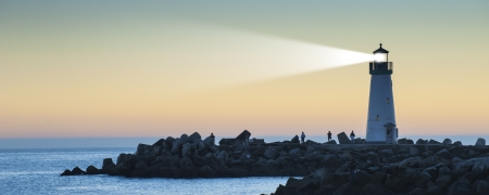 Foto de Lighthouse with light beam on ocean - Imagen libre de derechos