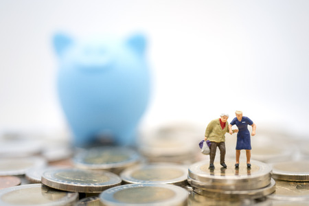 Foto de Miniature toy:Old man shopping or travel after retired on stack of coins and piggy bank. Saving money for after retire,business,shopping,travel concept - Imagen libre de derechos