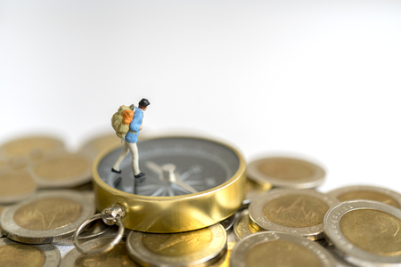 Photo for Miniature toy:Young hipster tourist planning saving money for tour on compass and coins : tour ,saving money ,adventure concept. - Royalty Free Image