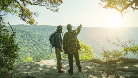 Photo pour Relaxed backpacker traveler talk with guide or park ranger about traget of point interest in deep forest,feel free and happy.Concept of vacation,freedom,happiness,enjoyment ,summer and well being. - image libre de droit