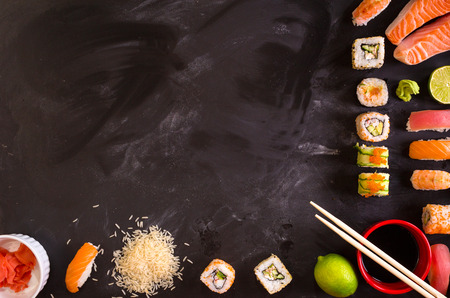 Photo pour Overhead shot of sushi and ingredients on dark background. Sushi rolls, nigiri, raw salmon steak, rice, cream cheese, avocado, lime, pickled ginger (gari), raw ginger, wasabi, soy sauce, nori, сhopsticks. Asian food background. Space for text - image libre de droit