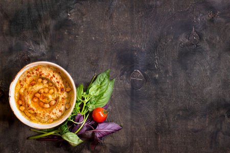 Foto de Hummus on a plate with cherry tomatoes and herbs on a dark wooden background. Middle eastern dish. Space for text - Imagen libre de derechos