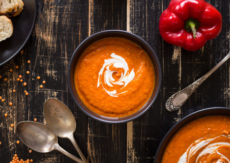 Photo pour Delicious pumpkin soup with heavy cream on dark rustic wooden table with red bell pepper, bread toasts, lentil. Top view - image libre de droit