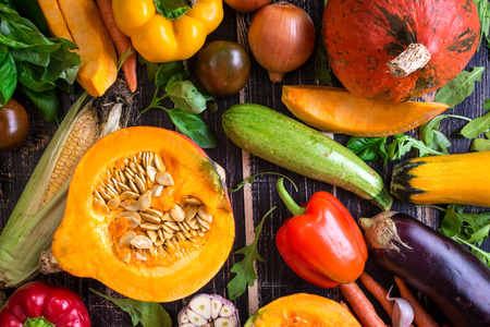 Photo for Fresh vegetables scattered on a old rustic dark textured table. Autumn background. Healthy eating. Sliced pumpkin, zucchini, squash, bell peppers, carrots, onions, cut garlic, tomatoes, eggplant, corn cob, rucola and basil. Top view - Royalty Free Image