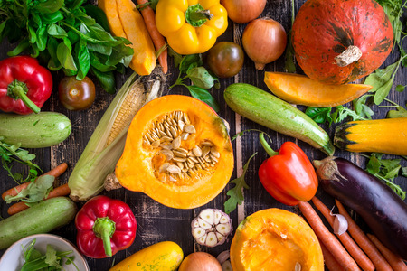 Fresh vegetables scattered on a old rustic dark textured table. Autumn background. Healthy eating. Sliced pumpkin, zucchini, squash, bell peppers, carrots, onions, cut garlic, tomatoes, eggplant, corn cob, rucola and basil. Top view