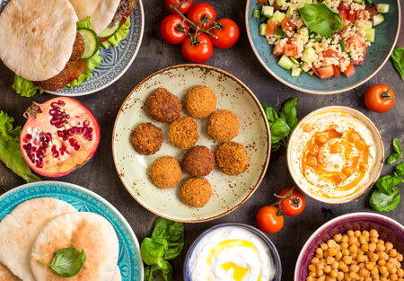 Foto de Table served with middle eastern traditional dishes. Bowl with falafel, doner kebap, vegetarian pita, hummus, tabbouleh bulgur salad, chickpea, olive oil dip, pomegranate. Top view. Dinner party - Imagen libre de derechos