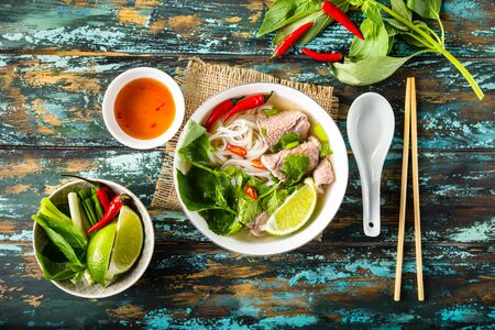 Photo for Traditional Vietnamese soup Pho bo with herbs, meat, rice noodles, broth. Pho bo in bowl with chopsticks, spoon. Space for text. Top view. Asian soup Pho bo on wooden table background. Vietnamese soup - Royalty Free Image