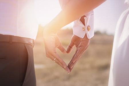 Foto de Holding Hands with wedding rings on the background of sunlight - Imagen libre de derechos