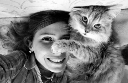 Woman taking photo of herself and her cat.