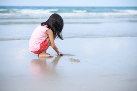 Little beautiful girl sitting and playing on white sand gorgeous beach against tranquil ocean and blue sky background