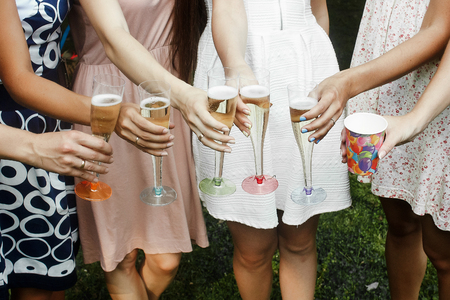 Photo pour hands of woman holding colorful glasses and toasting champagne at joyful party in summer park, bridal shower or wedding reception - image libre de droit