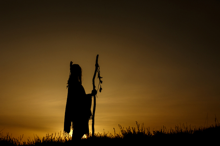 Photo pour silhouette of native american shaman with pikestaff on background of sunset beutiful in mountains - image libre de droit