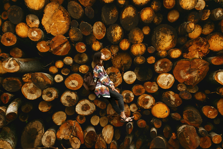 Photo pour stylish hipster woman with backpack sitting at pile of firewood, relaxing and thinking,  atmospheric moment, human scale, space for text - image libre de droit