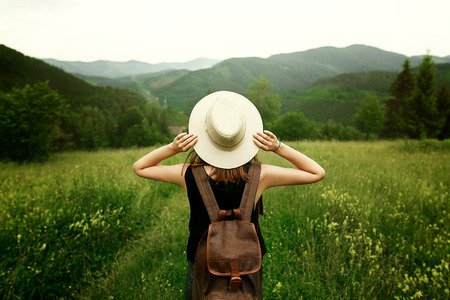 Photo pour woman traveler with backpack holding hat and looking at amazing mountains and forest, wanderlust travel concept, space for text, atmosperic epic moment - image libre de droit