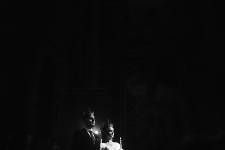 Photo for wedding ceremony at church. stylish groom and bride holding candles and giving vows. spiritual  sensual moment. space for text. black white photo - Royalty Free Image